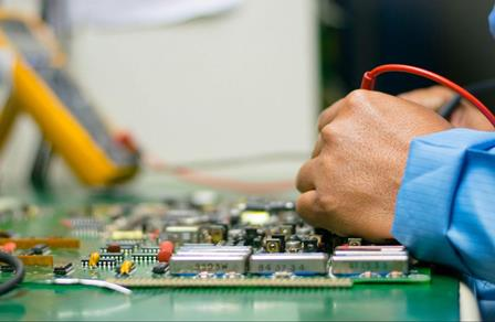 Engineer checking voltage on circut board.