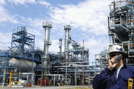 Engineer on phone at process plant checking safety.