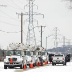 Electric Utility trucks parked in the snow amidst the Texas blackouts