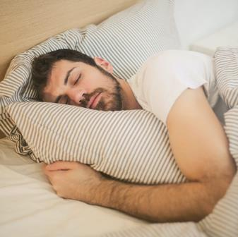 Man sleeping in bed to help him study more effectively